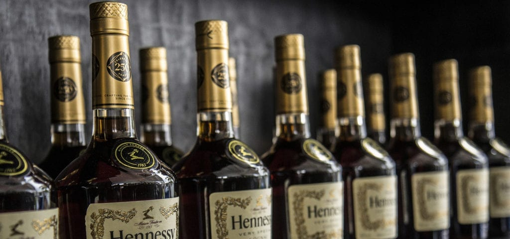 Bottles of Hennessy liquor lined up on the wall inside of a liquor store.