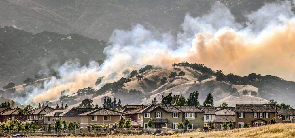 Wildfires encroach onto the backside of a California housing community.