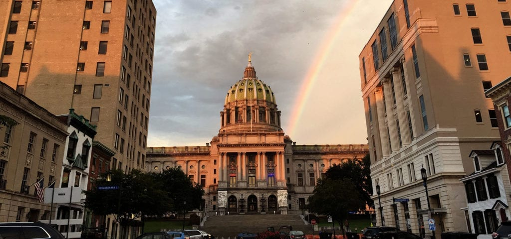 The Pennsylvavnia state capitol building in Harrisburg, Pennsylvania with a rainbow behind it.