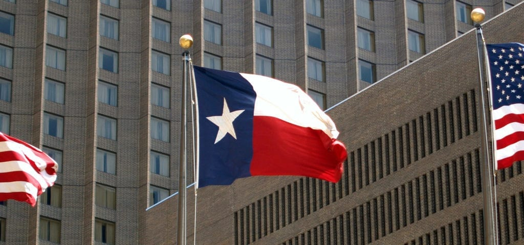The Lone Star State's state flag flying between two U.S. flags at the Texas state capitol building.
