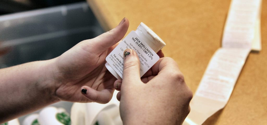 A cannabis budtender places a sticky label onto the packaging for an eighth of cannabis flower.