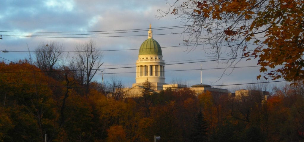 View of the Maine Statehouse in Augusta, Maine with autumn colors in the trees.