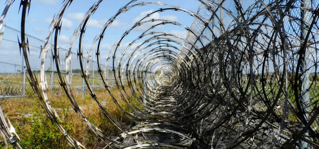 Prison barbed wire wrapped in circles around the top of a prison fence.
