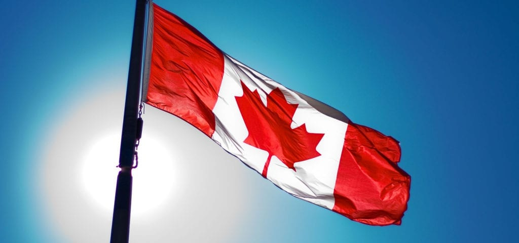 The national flag of Canada flies on a blue-skied, sunny day.