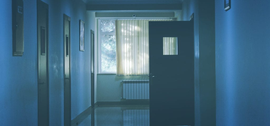 An open door at the end of a hospital hallway.