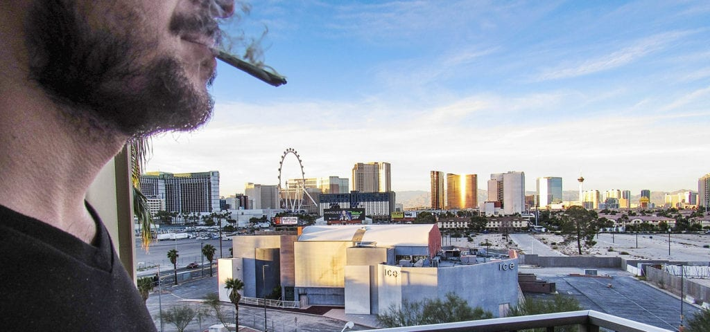 A man smoking a joint on a hotel balcony just outside of the Las Vegas strip.