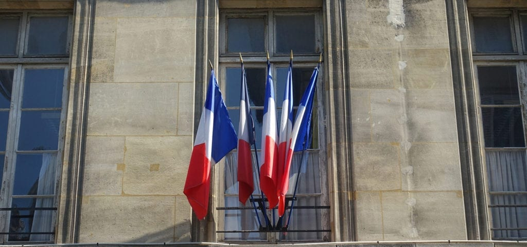 A row of French flags sticking out of a balcony in Paris. France.