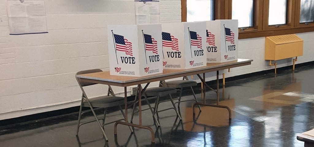 Voting booths set up temporarily in a school gymnasium.