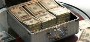 A briefcase packed full of cash sits open on a glass table, surrounded by more cash.