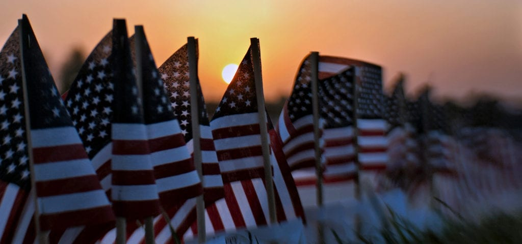 A sunset settling behind a row of small, toy American flags.