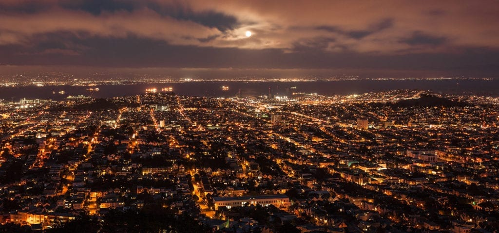 Nighttime view of the San Francisco sprawl with a full moon above it.