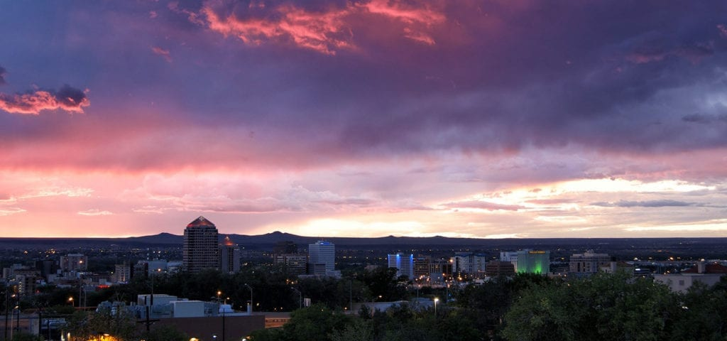 The Albuquerque skyline, photographed at sunset during a purple and blue hued sunset.
