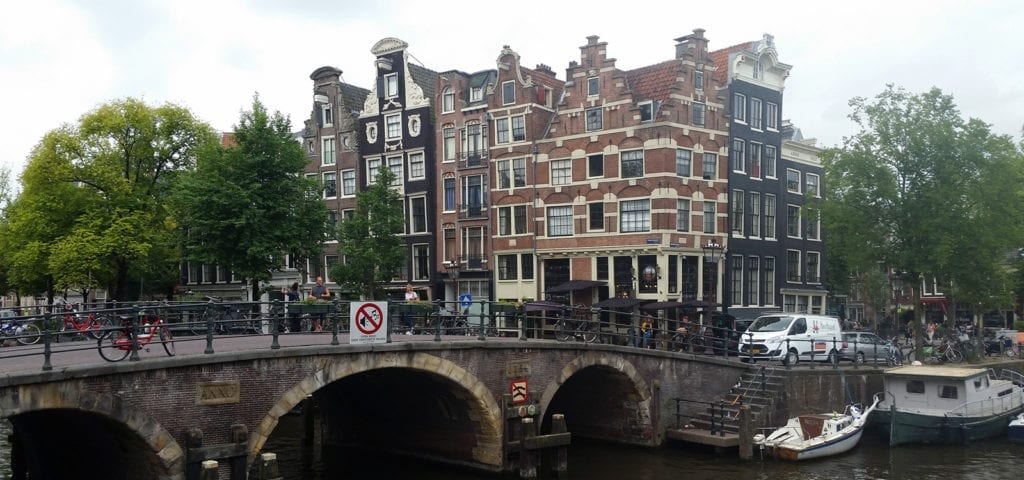 A bridge with people on it and houses behind it in Amsterdam.