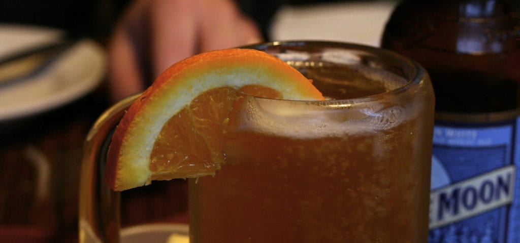 A blue moon beer poured into a chilled mug and served with an orange slice.