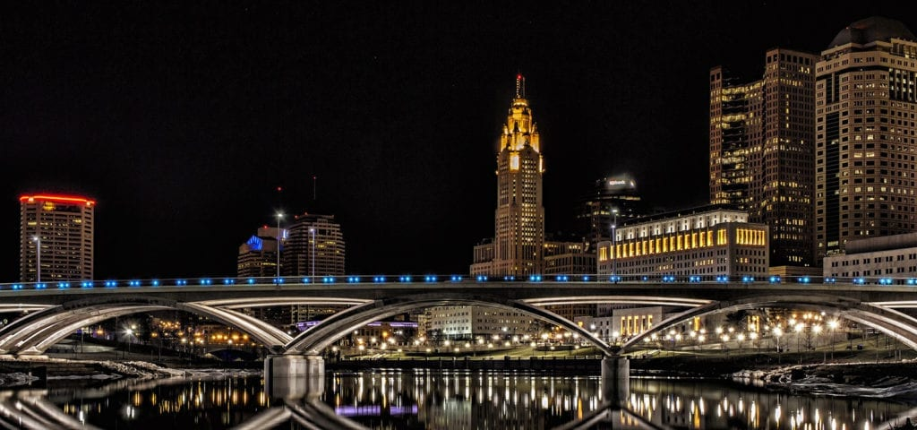 Nighttime photograph of a bridge in Columbus, Ohio with the city skyline behind it.