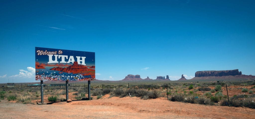 """A """"Welcome to Utah"""" sign alongside the road with several sandstone monuments on the horizon behind it."""