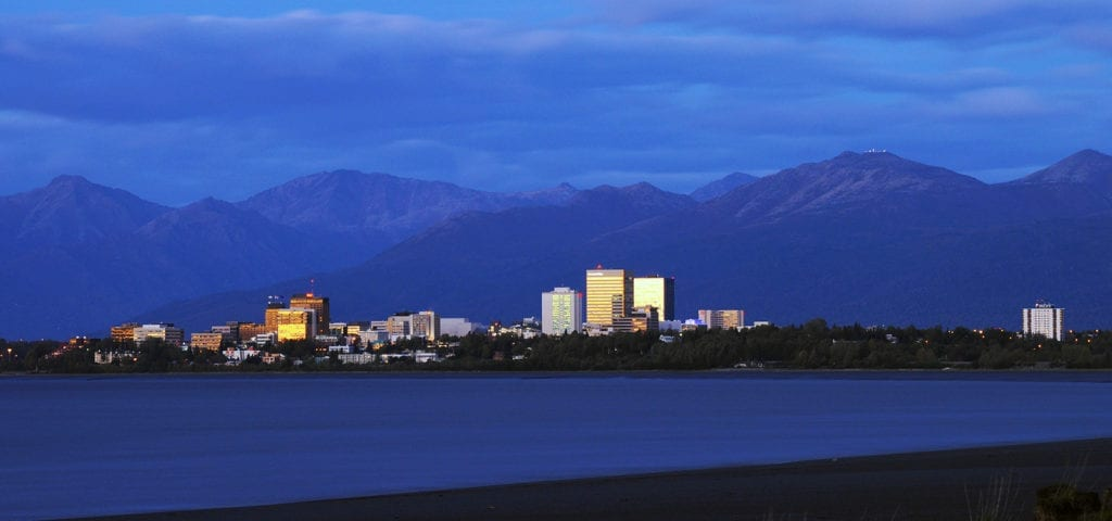 The Anchorage, Alaska city skyline, photographed from across a stretch of flat water.