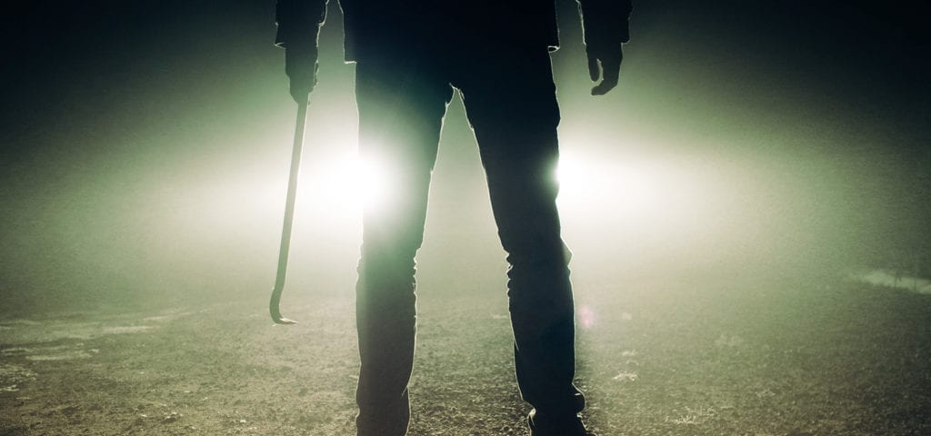A man stands in front of car headlights while holding a crowbar.