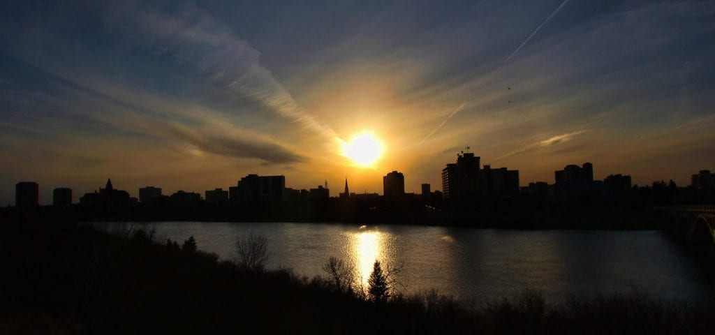 The city skyline of Saskatoon, Saskatchewan silhouetted by a setting sun.