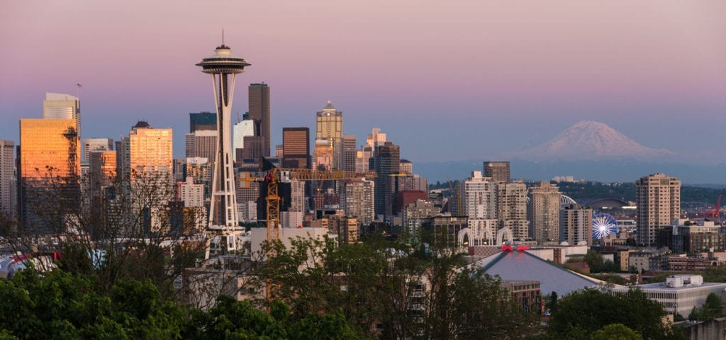 Photograph of a sunset view of Seattle, Washington with Mount Rainier in the background.
