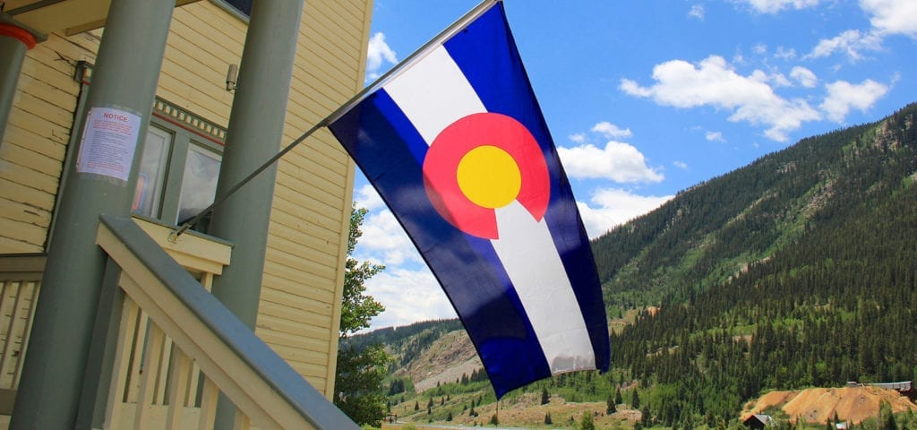 The Colorado state flag hangs off of the front porch of a large house located in the Rocky Mountains.