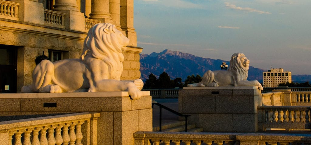 Two lion statues rest on either side of a marble stairway leading up to the Utah State Capitol Building in Salt Lake City, Utah.